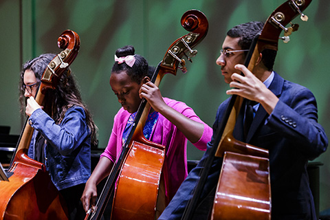 Three musicians from the Shalala Music Outreach program are performing with cellos on stage