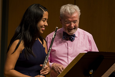 A man with white hair smiles while looking down as a woman to his right is holding a flute