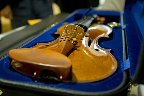 A light brown violin is sitting in a blue lined carrying case with the top propped up